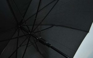 Opened umbrella made of black fabric, metal tube and glass fiber ribs for best quality and design.